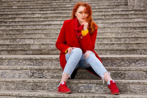 Na Schodach Na Zewnątrz Siedzi Miła Młoda Kobieta Z Rudymi Włosami, W Czerwonym Płaszczu I Dżinsach Darmowe Zdjęcia
