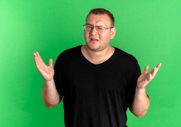Nad Zieloną ścianą Mężczyzna Z Nadwagą W Okularach I Czarnym T-shircie Wygląda Na Zdezorientowanego, Wzruszając Ramionami Darmowe Zdjęcia