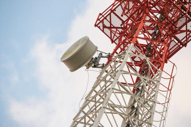 Nadajnik Anteny Komunikacji Bezprzewodowej. Wieża Telekomunikacyjna Z Antenami Na Niebieskim Tle Nieba. Premium Zdjęcia