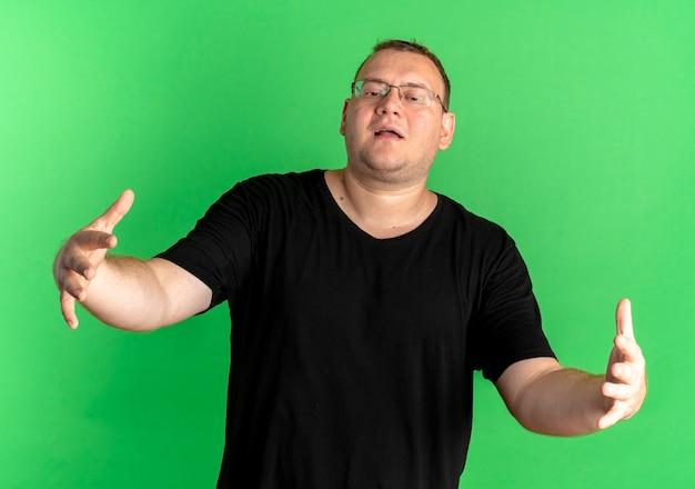 Nadwaga Mężczyzna W Okularach Na Sobie Czarną Koszulkę Robi Powitalny Gest Szeroko Otwierając Ręce Stojąc Na Zielonej ścianie Darmowe Zdjęcia