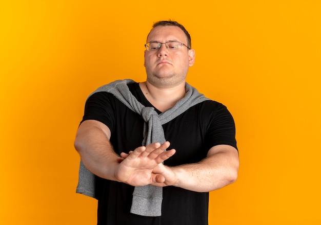 Nadwaga Mężczyzna W Okularach Na Sobie Czarną Koszulkę Robi Znak Stopu Z Poważną Twarzą Stojącą Nad Pomarańczową ścianą Darmowe Zdjęcia