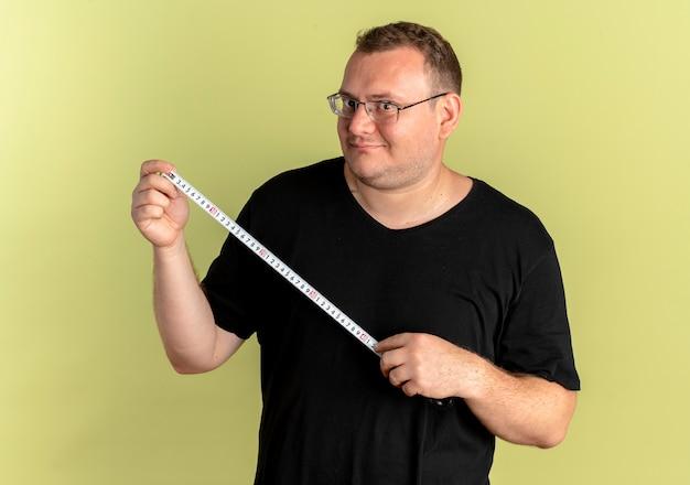 Nadwaga Mężczyzna W Okularach Na Sobie Czarną Koszulkę Trzyma Linijkę Z Uśmiechem Na Twarzy Stojącej Nad Jasną ścianą Darmowe Zdjęcia