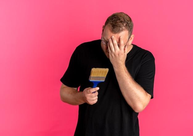 Nadwaga Mężczyzna W Okularach Na Sobie Czarną Koszulkę, Trzymając Pędzel Zakrywający Twarz Ręką Rozczarowany Stojąc Nad Różową ścianą Darmowe Zdjęcia
