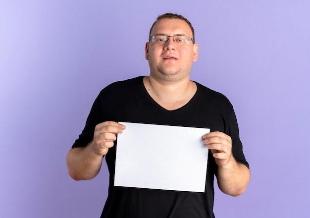 Nadwaga Mężczyzna W Okularach Na Sobie Czarną Koszulkę, Trzymając Pusty Arkusz Papieru Z Uśmiechem Stojący Nad Niebieską ścianą Darmowe Zdjęcia