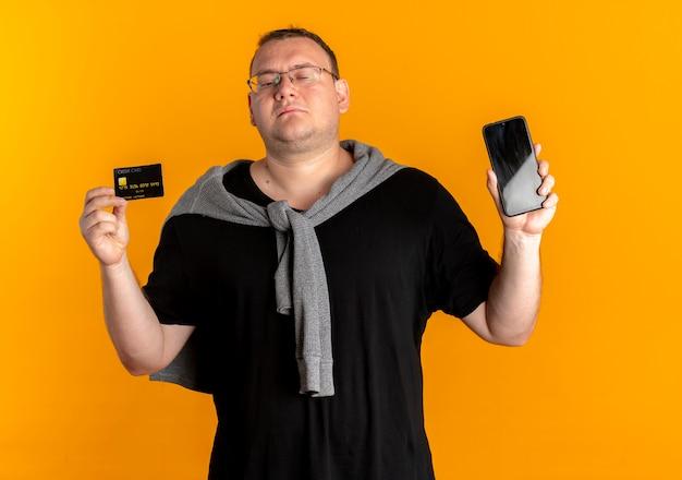 Nadwaga Mężczyzna W Okularach Na Sobie Czarną Koszulkę, Trzymając Smartfon Pokazując Kartę Kredytową, Patrząc Pewnie Na Pomarańczowo Darmowe Zdjęcia