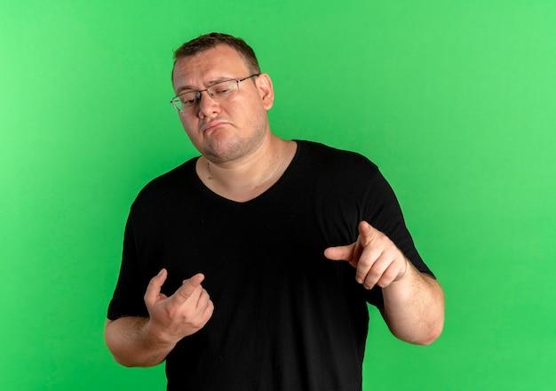 Nadwaga Mężczyzna W Okularach Na Sobie Czarną Koszulkę, Wskazując Palcami Wskazującymi, Stojąc Na Zielonej ścianie Darmowe Zdjęcia