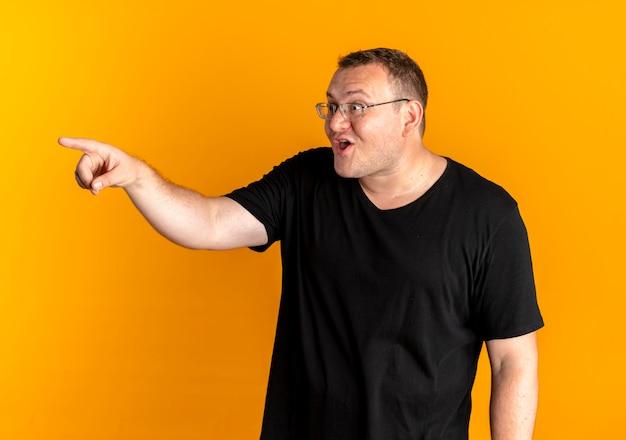 Nadwaga Mężczyzna W Okularach Na Sobie Czarną Koszulkę, Wskazując Palcem Na Coś Szczęśliwego I Podekscytowanego Stojącego Nad Pomarańczową ścianą Darmowe Zdjęcia