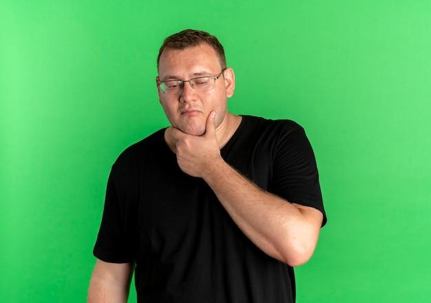 Nadwaga Mężczyzna W Okularach Na Sobie Czarną Koszulkę Z Ręką Na Brodzie Z Zamyślonym Wyrazem Twarzy Stojącej Nad Zieloną ścianą Darmowe Zdjęcia