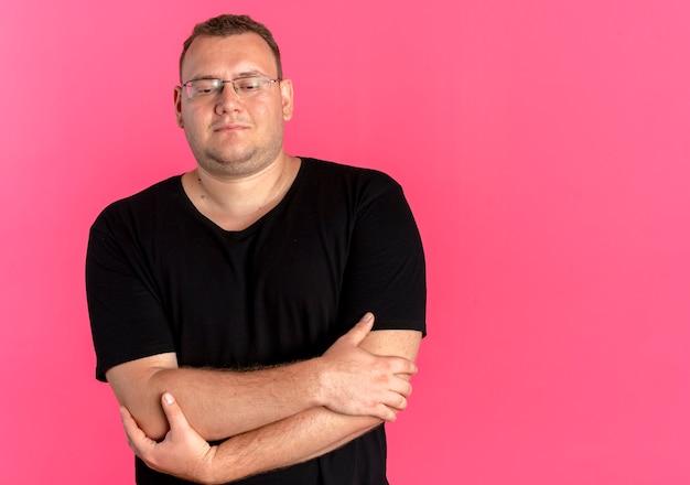 Nadwaga Mężczyzna W Okularach Na Sobie Czarną Koszulkę Z Uśmiechem Na Twarzy Z Rękami Skrzyżowanymi Na Piersi, Stojący Nad Różową ścianą Darmowe Zdjęcia