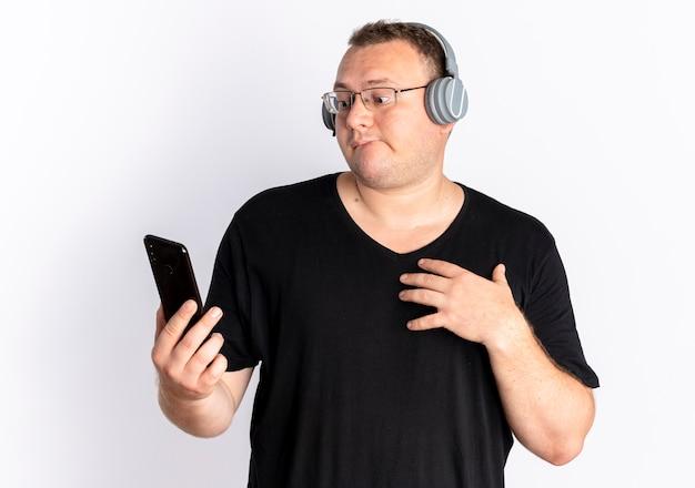 Nadwaga Mężczyzna W Okularach Na Sobie Czarną Koszulkę Ze Słuchawkami, Trzymając Smartfon Patrząc Na Ekran Zdezorientowany Stojąc Na Białej ścianie Darmowe Zdjęcia