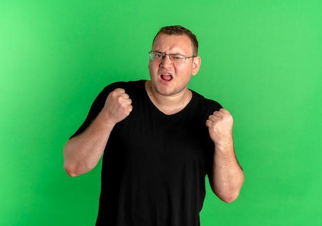 Nadwaga Mężczyzna W Okularach Ubrany W Czarny T-shirt Zaciskając Pięści Szczęśliwy I Podekscytowany Stoi Nad Zieloną ścianą Darmowe Zdjęcia