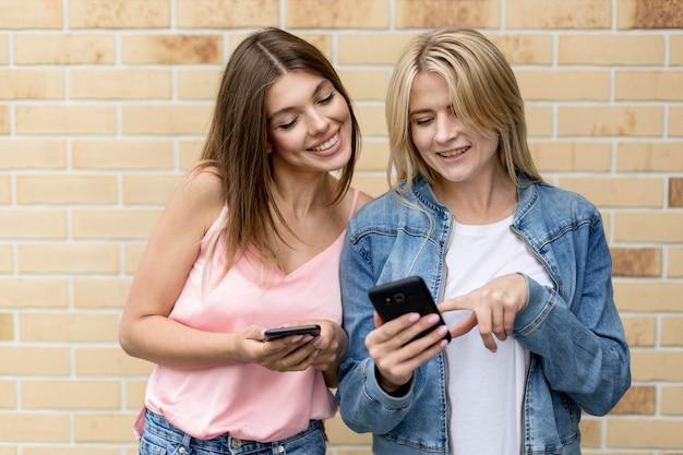 Najlepsi Przyjaciele Patrzą Na Swoje Telefony Komórkowe Na Zewnątrz Darmowe Zdjęcia