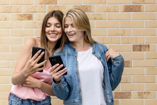 Najlepsi Przyjaciele Patrzą Na Swoje Telefony Komórkowe Darmowe Zdjęcia