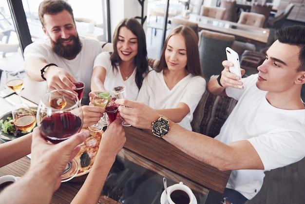 Najlepsi Przyjaciele Spotkali Się Przy Stole Przy Pysznym Jedzeniu I Kieliszkach Czerwonego Wina, Aby Uczcić Wyjątkową Okazję. Premium Zdjęcia
