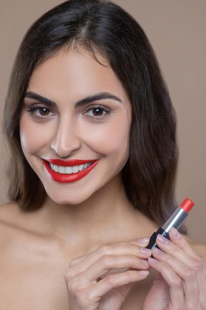 Najlepsza Szminka. Zadowolona Twarz Ciemnowłosej Kobiety Z Czerwoną Szminką Na Ustach Trzymająca Walizkę W Dłoniach Premium Zdjęcia