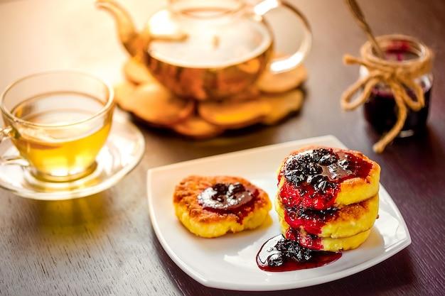 Naleśniki ze słodkim serem na białym talerzu z zieloną herbatą rumiankową. selektywne ustawianie ostrości. Premium Zdjęcia