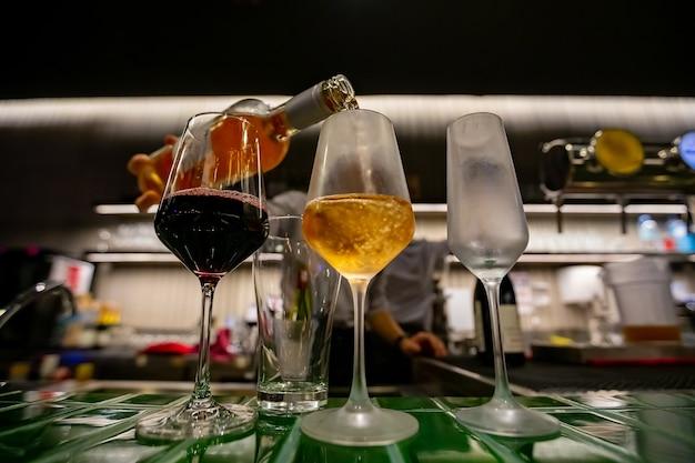 Nalewanie Trzech Kieliszków Wina Z Butelki Wina Premium Zdjęcia