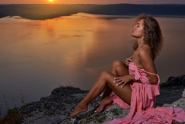 Namiętny Model Pozowanie, Siedząc Na Tle Zachodu Słońca. Premium Zdjęcia
