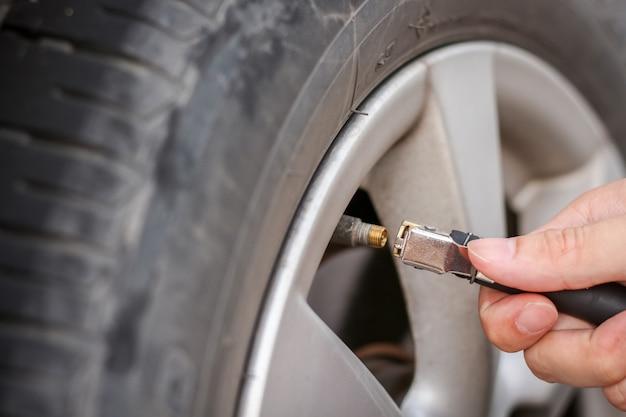 Napełnianie powietrza do grungy opony samochodowej w celu zwiększenia ciśnienia Premium Zdjęcia