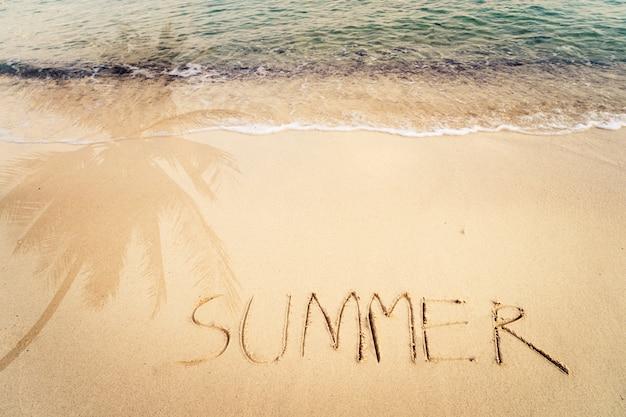 Napis Napisany Na Piaszczystej Plaży Z Falą Oceanu I Palmy Bez Cienia. Vintage Efekt Kolorystyczny Premium Zdjęcia