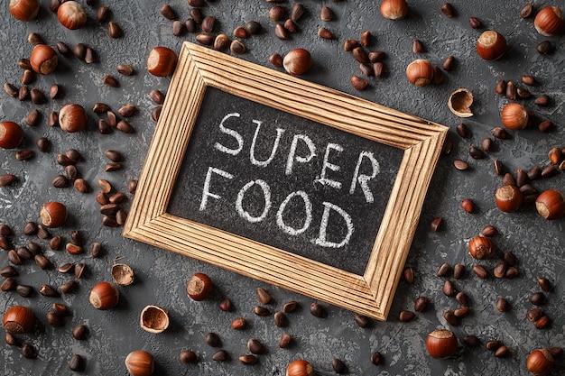 Napis super food, różne orzechy na kamiennym stole Premium Zdjęcia