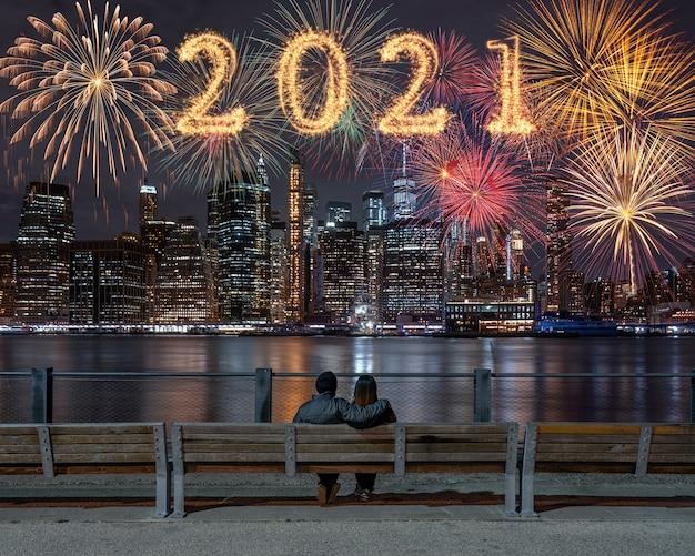 Napisane Z Fajerwerkami Sparkle Z Wielokolorowymi Fajerwerkami Na Odwrocie Para Siedzi I Patrzy New York Cityscape Background Premium Zdjęcia