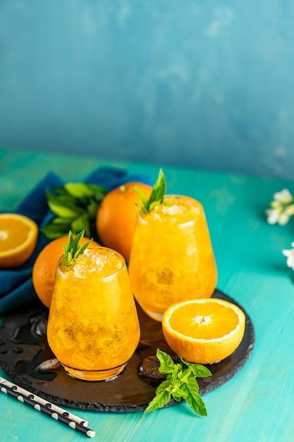 Napój Pomarańczowy Z Lodem. Dwie Szklanki Napoju Pomarańczowego Z świeżą Miętą Premium Zdjęcia