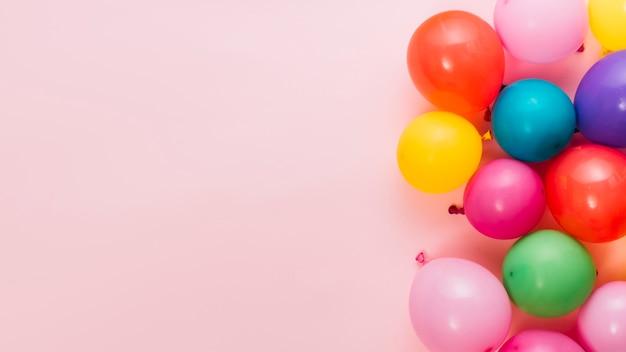 Napompowane kolorowe balony na różowym tle z miejsca do pisania tekstu Darmowe Zdjęcia