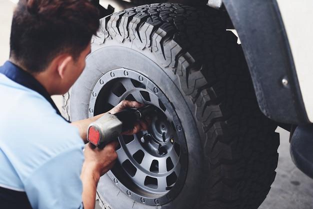 Naprawa Lub Zmiana Mechanika Pickup Opon Samochodowych Przykręcanie Odkręcania Koła Samochodu W Serwisie Naprawczym Premium Zdjęcia