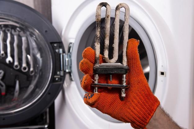 Naprawa Pralek. Ręka Mechanika Z Turbulentną Grzałką Elektryczną Pokrytą Warstwą Twardej Wody. Premium Zdjęcia