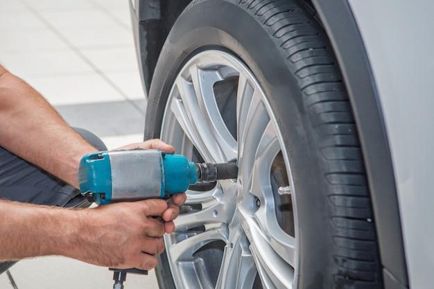 Naprawa Samochodów: Zbliżenie Wymiany Koła. Mechanik Przykręcania Lub Odkręcania Koła Samochodu W Garażu Serwisu Samochodowego Premium Zdjęcia