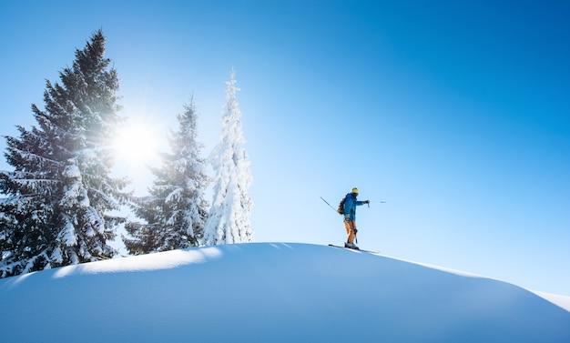 Narciarz na szczycie góry, wskazując na niebo Premium Zdjęcia