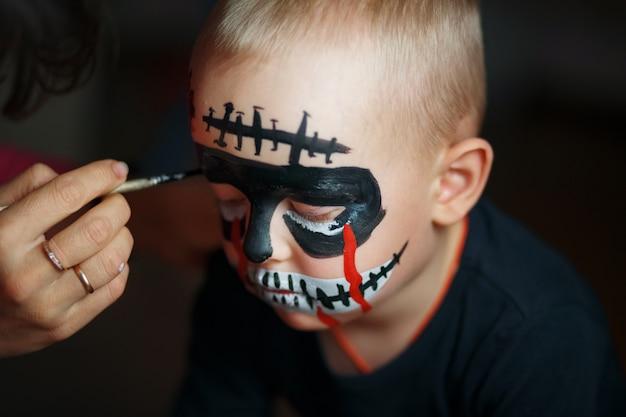 Narysuj twarz chłopca. emocjonalny portret z przerażającym zombie na twarzy Premium Zdjęcia