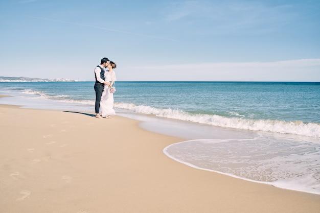 Narzeczeni Całuje Się Na Plaży W Sukniach ślubnych Premium Zdjęcia