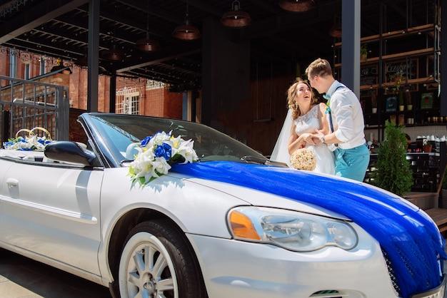 Narzeczeni są fotografowani w pobliżu samochodu Premium Zdjęcia