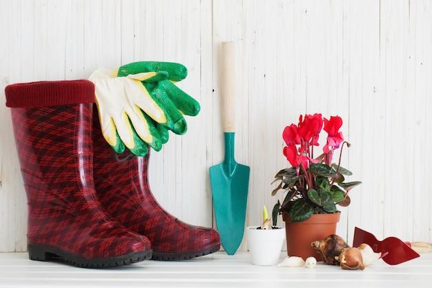 Narzędzia Ogrodnicze I Gumowe Buty Na Białym Drewnianym Stole Premium Zdjęcia