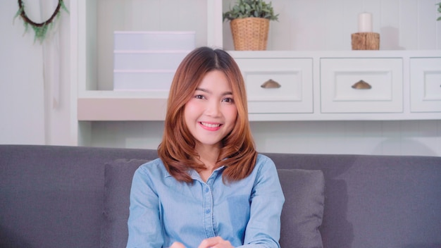 Nastolatek Azjatycka Kobieta Czuje Szczęśliwego Uśmiechniętego I Patrzeje Kamera Podczas Gdy Relaksuje W Jej żywym Pokoju Darmowe Zdjęcia