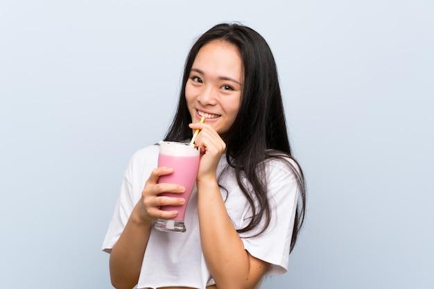 Nastolatek azjatykcia dziewczyna trzyma truskawkowego milkshake Premium Zdjęcia