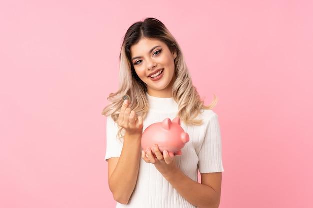 Nastolatek dziewczyna nad odosobnionym różowym tłem trzyma dużego piggybank Premium Zdjęcia