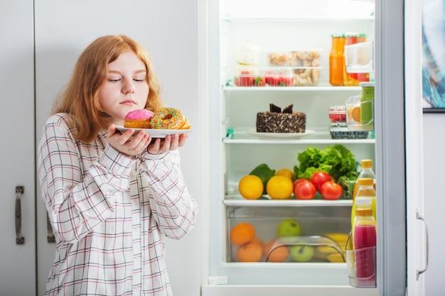 Nastolatek Dziewczyna Przy Lodówką Z Jedzeniem Premium Zdjęcia