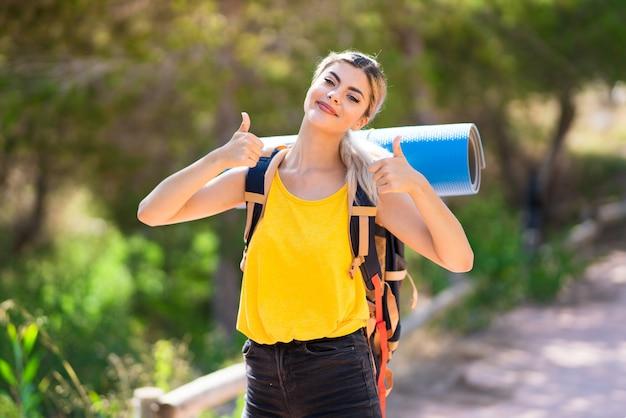 Nastolatek Dziewczyna Wycieczkuje Przy Outdoors Z Aprobata Gestem I Ono Uśmiecha Się Premium Zdjęcia