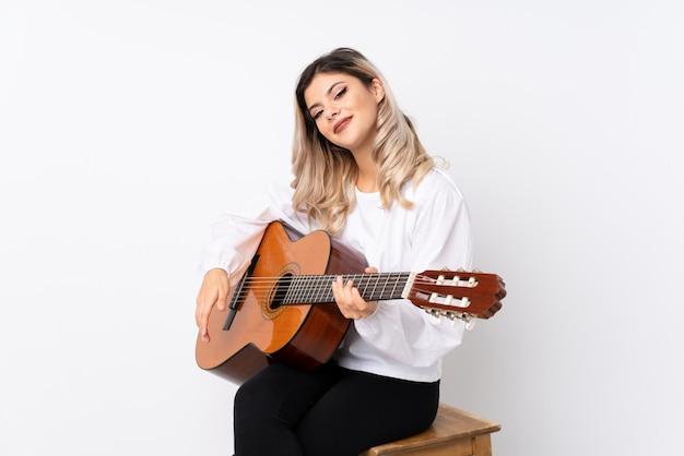 Nastolatek dziewczyna z gitarą nad odosobnionym białym tłem ono uśmiecha się dużo Premium Zdjęcia