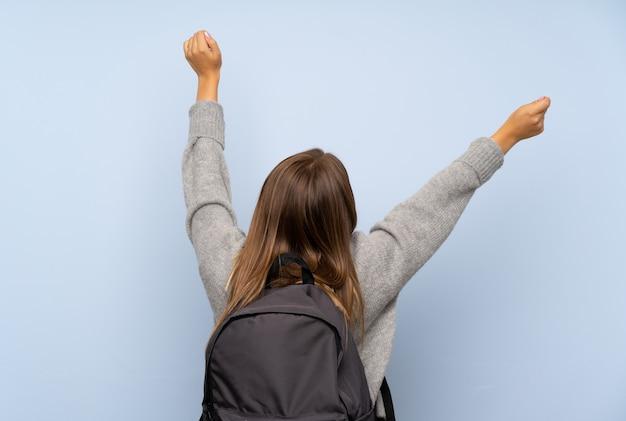 Nastolatek dziewczyna z pulowerem odizolowywającym nad z plecakiem Premium Zdjęcia
