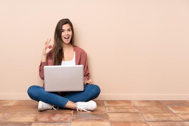 Nastolatek Dziewczyny Studencki Obsiadanie Na Podłoga Z Laptopem Zaskakującym I Pokazuje Ok Znaka Premium Zdjęcia