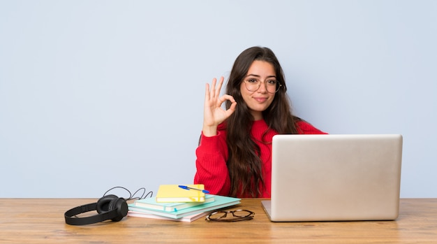 Nastolatek dziewczyny studencki studiowanie w stole pokazuje ok znaka z palcami Premium Zdjęcia