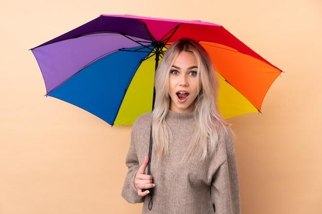 Nastolatek Kobieta Trzyma Parasol Nad Odosobnioną ścianą Z Niespodzianka Wyrazem Twarzy Premium Zdjęcia