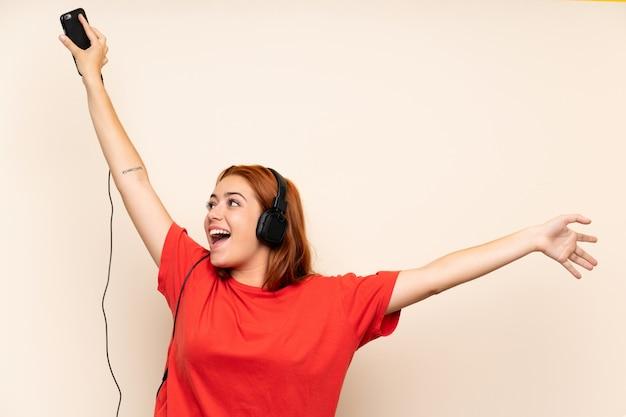 Nastolatek ruda dziewczyna słuchania muzyki za pomocą telefonu komórkowego Premium Zdjęcia