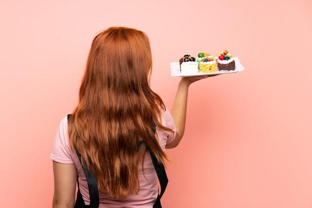 Nastolatek Ruda Dziewczyna Trzyma Mnóstwo Różnych Mini Ciasta Na Pojedyncze Różowe Tło W Tylnej Pozycji Premium Zdjęcia