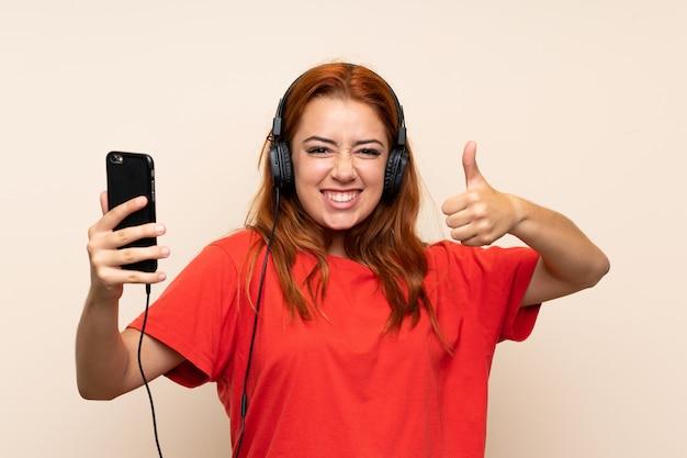 Nastolatek rude dziewczyny słuchania muzyki z telefonu komórkowego z kciukiem do góry Premium Zdjęcia