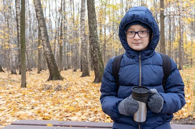 Nastolatek Siedzi Na ławce W Jesiennym Parku Z Kubkiem Termicznym Wypełnionym Gorącym Napojem, Kawą Premium Zdjęcia